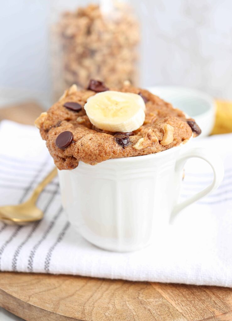 a white mug with banana cake with chocolate chips and a slice of banana on a wooden board on a white napkin with a golden spoon on the left