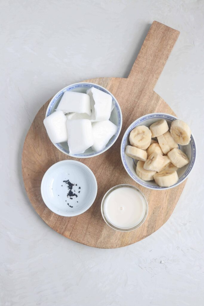 prepared ingredients in bowls of coconut, banana, almond milk, and vanilla beans.