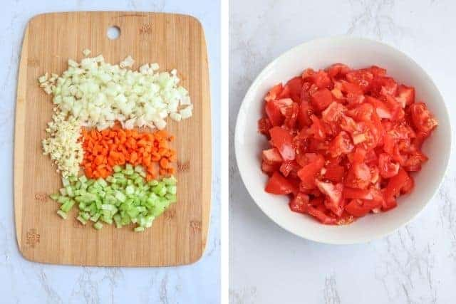 a wooden board with chopped onions, garlic, carrots and celery, and a white bowl with chopped fresh tomatoes