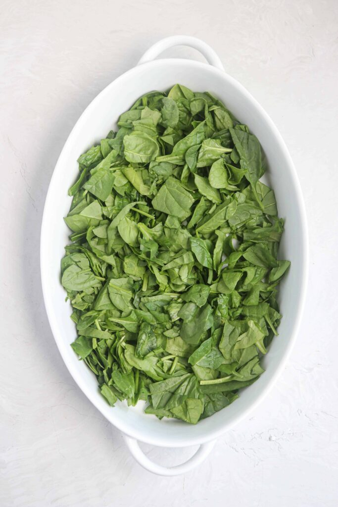an oval dish with chopped baby spinach
