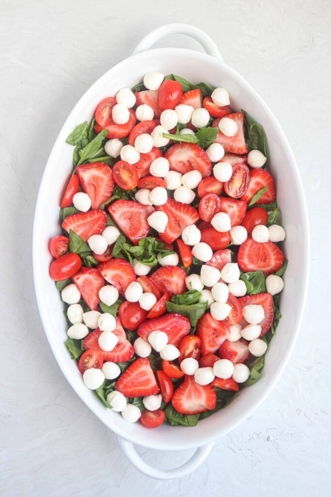 an oval dish with chopped baby spinach, strawberries and cherry tomatoes and mozzarella balls