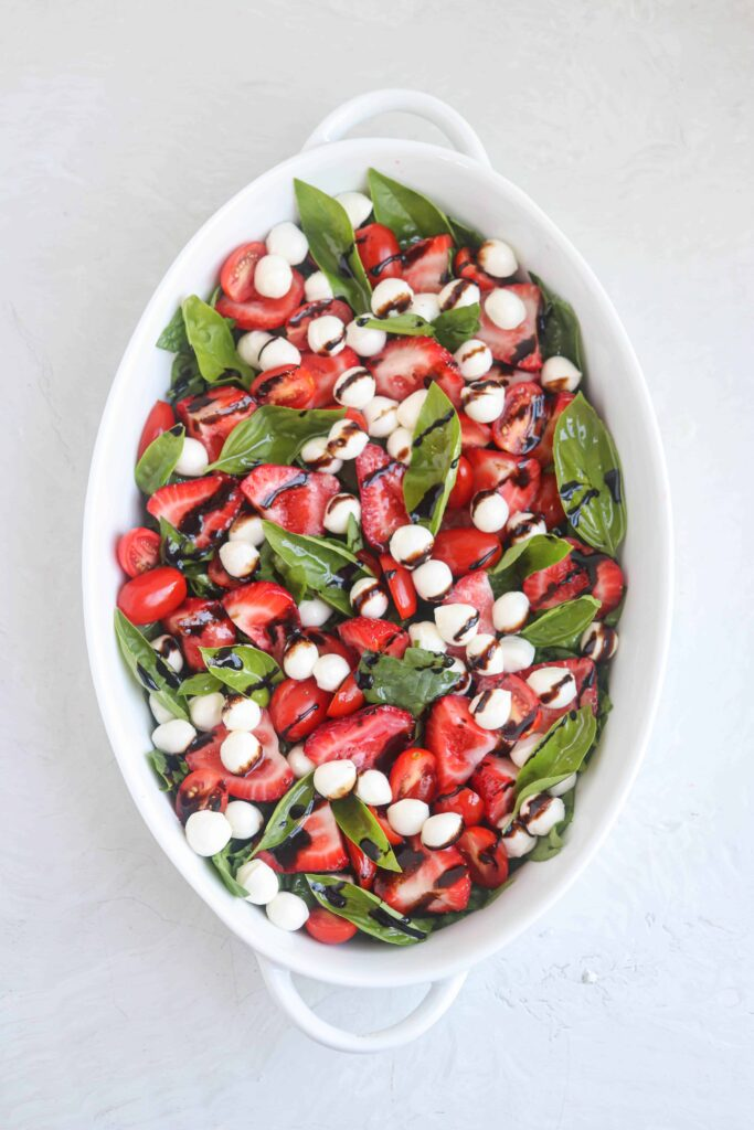 strawberry spinach caprese salad served in an oval casserole dish on light gray surface