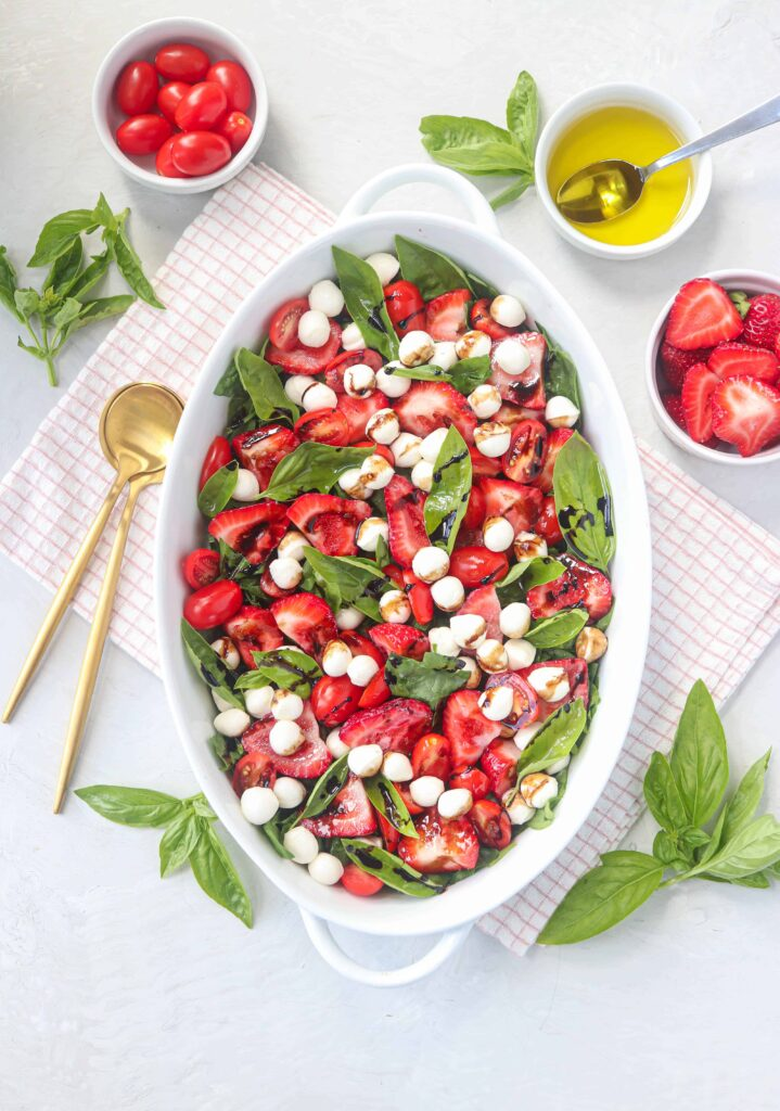 strawberry spinach caprese salad served in an oval casserole dish on light gray surface on a red a white kitchen towel