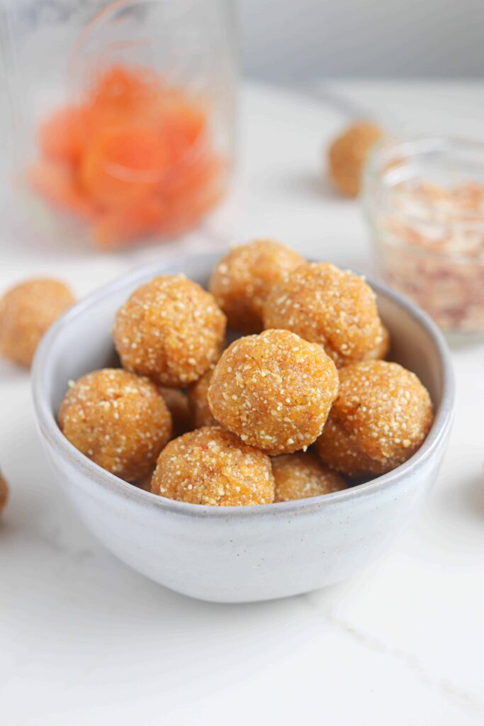 a light gray bowl with healthy apricot bliss balls on a light surface
