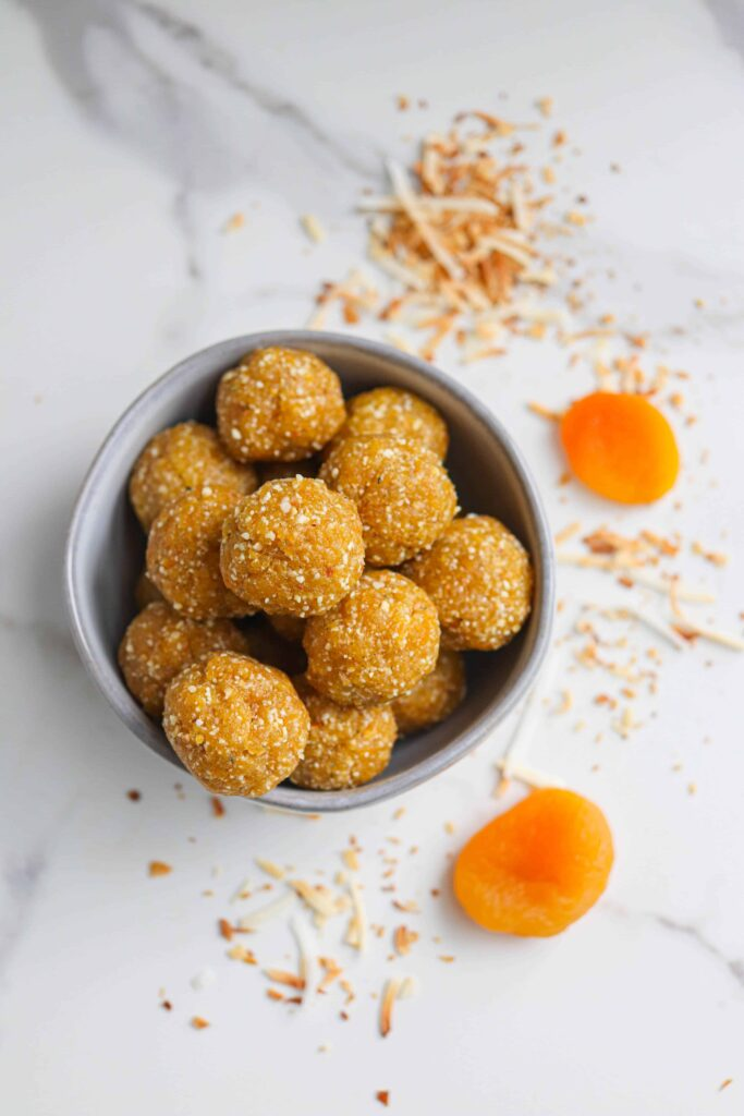 a light gray bowl with healthy apricot bliss balls on a light surface, overhead shot with 2 dried apricots and toasted coconut scattered around the bowl