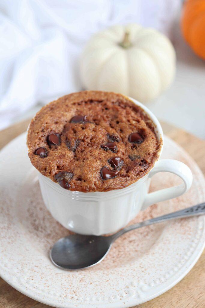 pumpkin mug cake in a white teacup on a saucer