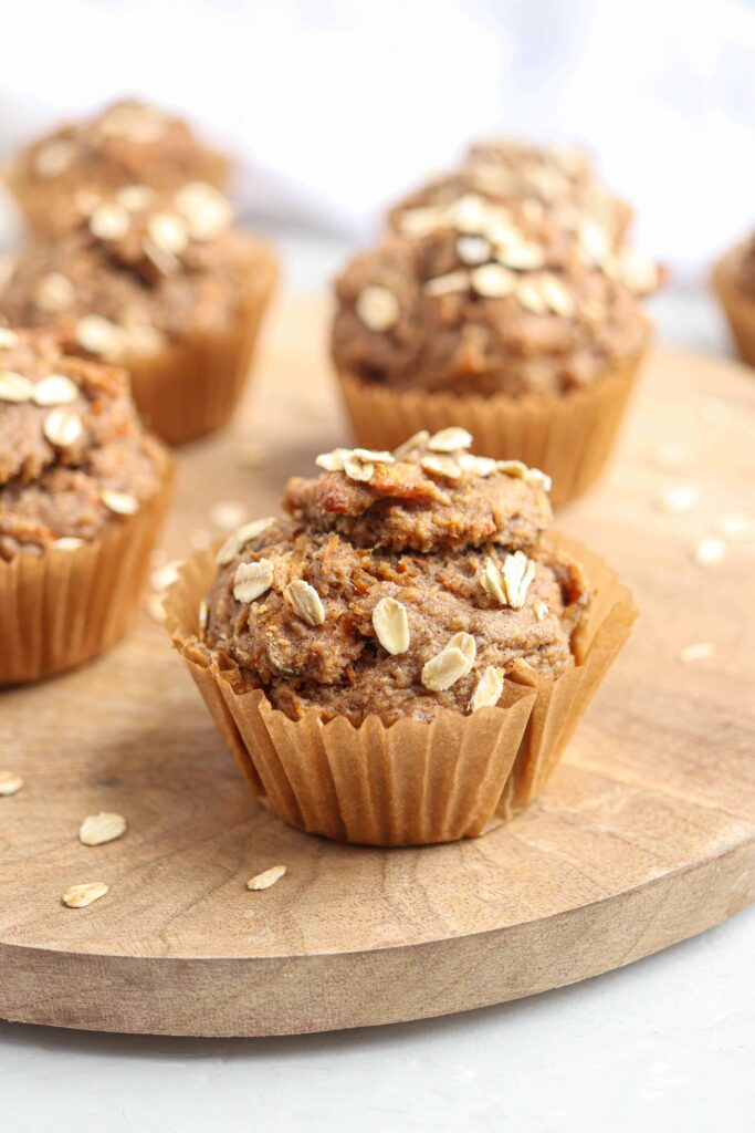 banana carrot oat muffins on a round wooden board on light gray surface