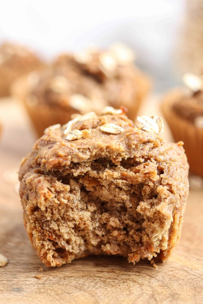 bite shot of banana carrot oat muffins on a round wooden board on light gray surface