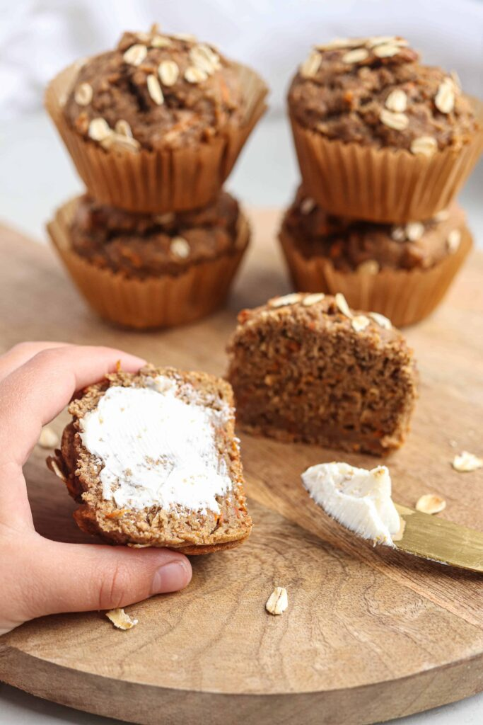 banana carrot oat muffins on a round wooden board on light gray surface, one muffin being buttered
