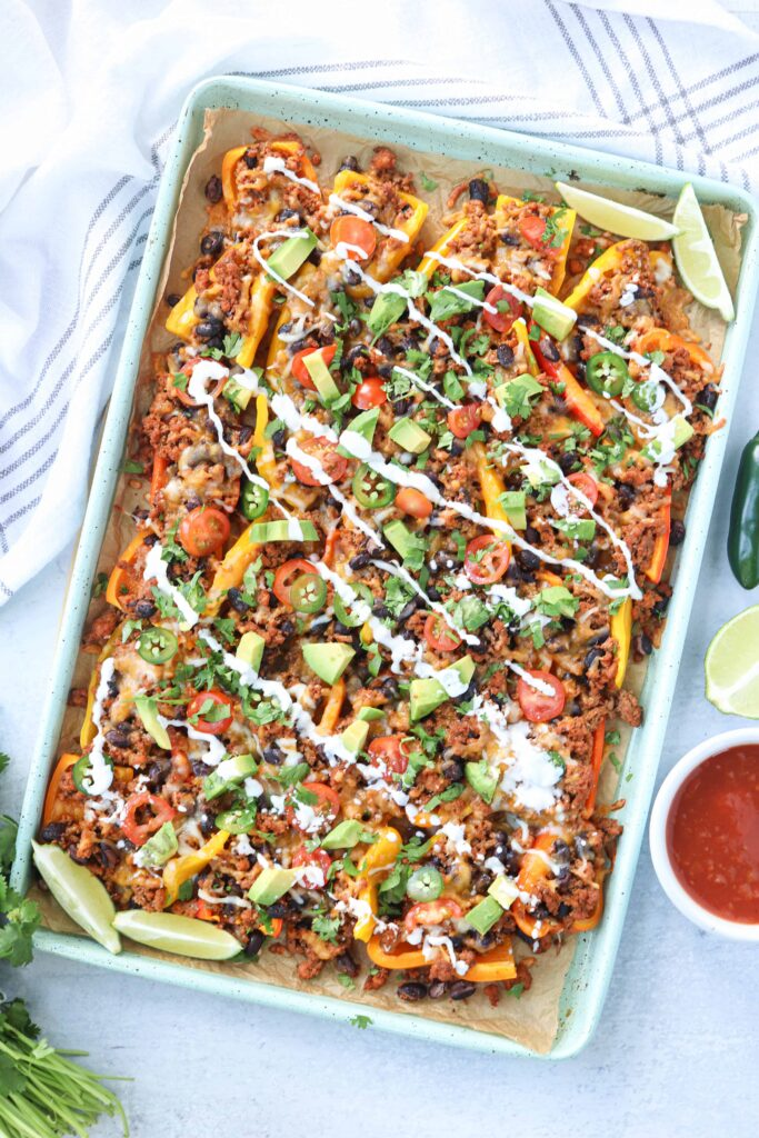 a baking sheet with mini pepper loaded nachos on light gray surface