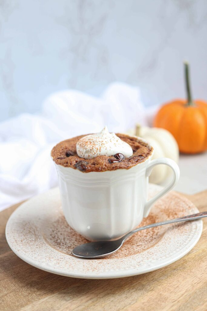 pumpkin mug cake with a dollop of whipped cream and cinnamon in a white teacup on a saucer